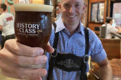 Guy in lederhosen handing you a beer.