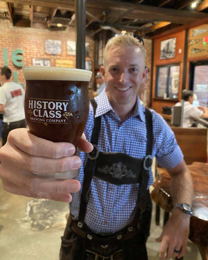 Guy in lederhosen holding a beer. Find fun things to do near our PCB beach rentals.